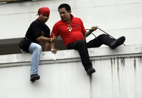 Arisman Pongruengrong fugge braccato dalla polizia calandosi da un balcone