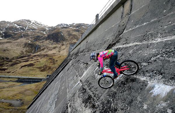 Adam Flint in bici sulla parete di una diga