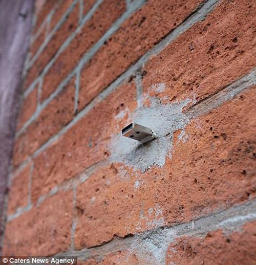 Un muro da cui spunta una pendrive USB