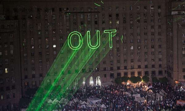 La scritta 'out' con un laser sui muri del Cairo