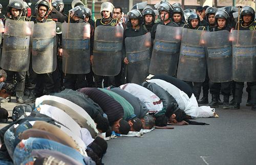 Fedeli in preghiera al Cairo circondati da poliziotti in tenuta antisommossa