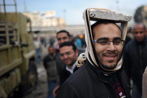 Un manifestante egiziano improvvisa un casco