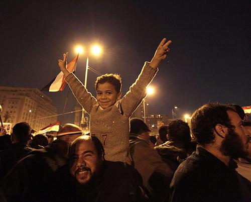 Un bambino in braccio al padre festeggia la cacciata di Mubarak