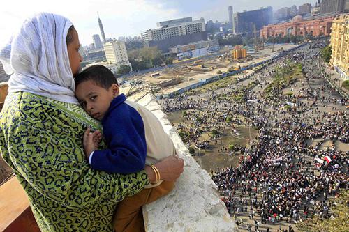 Una madre col figlio guarda piazza Tahrir