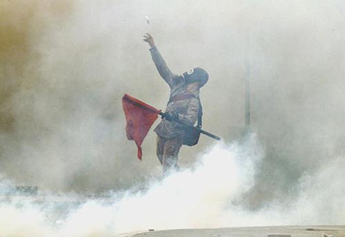 Dimostrante greco tra i fumogeni della polizia ad Atene