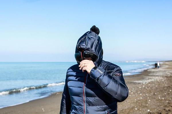 Beppe Grillo con cappuccio vestito da guitto in spiaggia