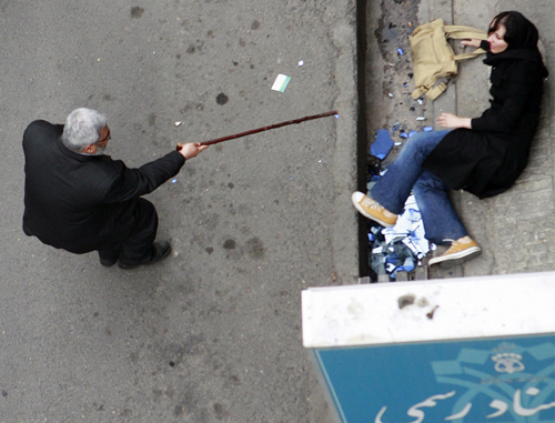 A man with a cane gestures towards a woman on the ground during protests in central Tehran