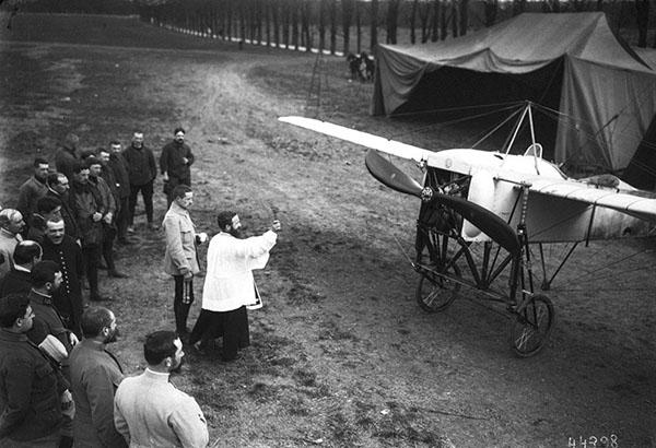 Un prete benedice un aereplano da guerra