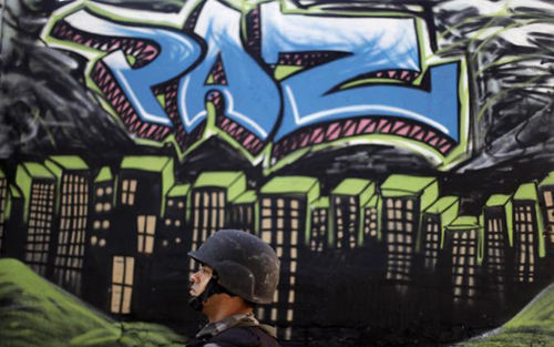Un soldato di guardia sotto un murales in una favela di Rio
