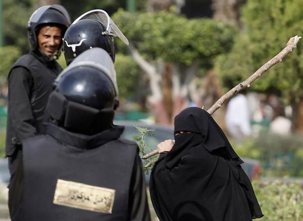 Una donna egiziana con un ramo tra poliziotti